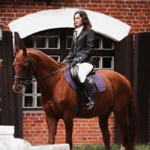 Dame der ride på en hest udenfor en af de store rideklubber i Danmark